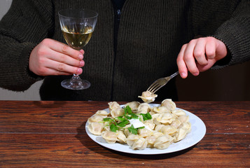 Man's hands hold a glass of wine and a plug with pelmeni