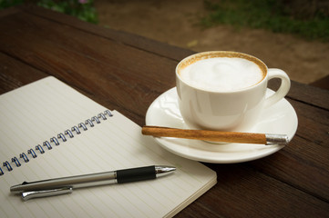 Coffee cup with pen and book.