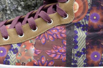 Detalle de una zapatilla de deporte con flores estampadas.