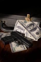 Gun and dollar bill in briefcase.