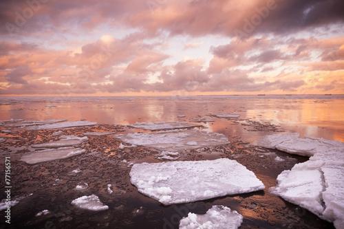Winter coastal landscape with melting ice fragments