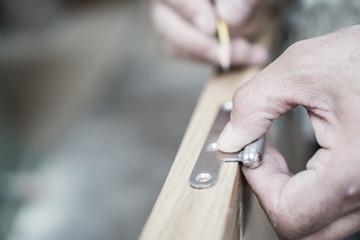 Closeup of carpenter hand with pencil working on door hinge