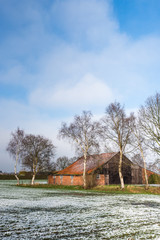 Historic agricultural barn in a rural landscape with snow.