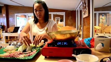 Thai women cooking Sukiyaki or Shabu Shabu or Hot Pot
