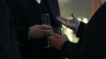 Man in black suit hold glass with champagne and drinks it