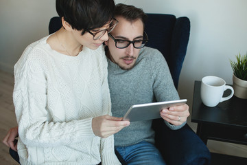 Hipster couple in eyewear enjoying the tablet together