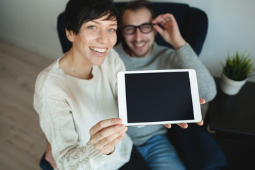 Hipster couple in eyewear showing the screen of tablet