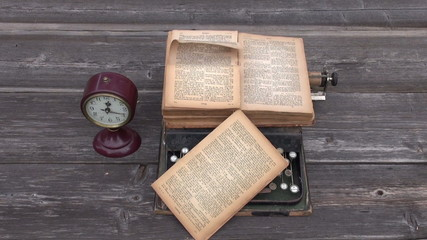 ancient typewriter and old Bible book on wooden background