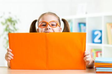 clever kid little girl behind of open book indoor