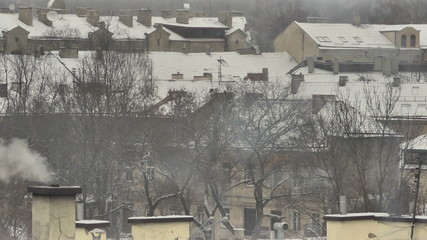 Vilnius. Winter. Snow-covered roof. Сhimneys smoke. Zoom out