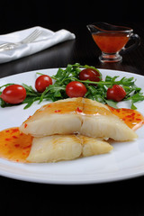 Flounder fillets in sauce with arugula and cherry tomatoes