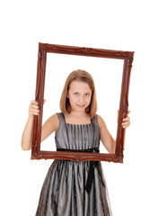 Pretty girl holding picture frame.