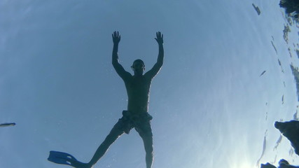 man snorkeling and floats through the frame, inside view