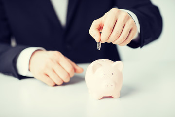 man putting coin into small piggy bank