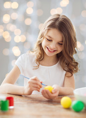 close up of girl with brush coloring easter eggs