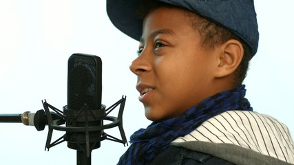 cute african boy sings the song in the studio