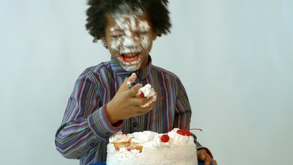 black boy eating messily  cake hands