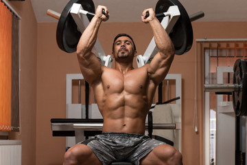 Bodybuilder Doing Heavy Weight Exercise For Shoulders