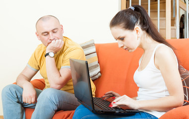 Woman   with laptop and her husband at home