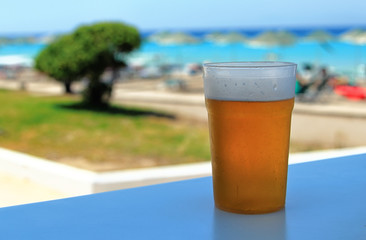 glass of beer on a table at the beach background