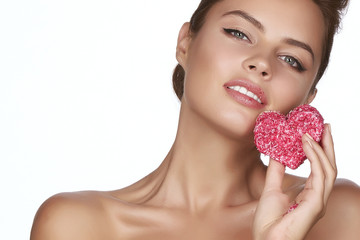 Beautiful sexy woman eating cake shape of heart valentine day .