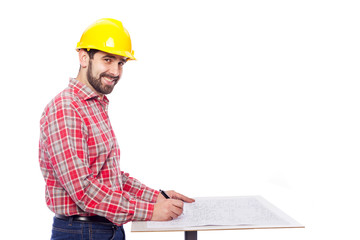 Smiling architect drawing on blueprint, isolated on white backgr