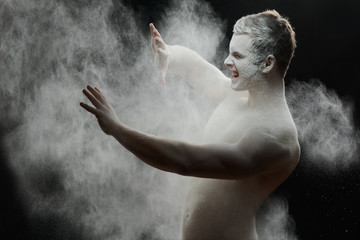 Handsome frozen man with a white powder on his body