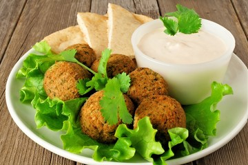 Plate of falafel on lettuce with pita bread and tzatziki sauce