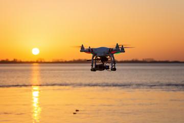 Fliegende Kameradrohne vor Sonnenuntergang