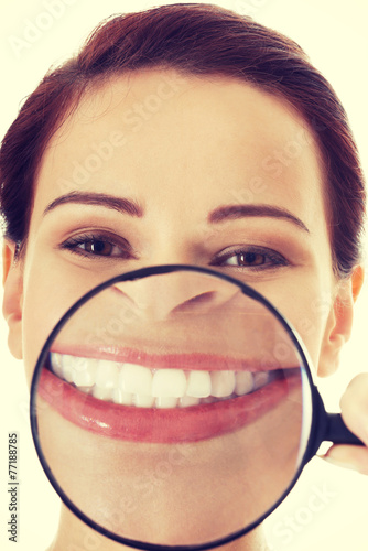 canvas print picture Young woman with magnifying glass on mouth.