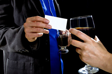 businessman handing over businesscard to a female at a bar