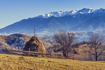 Alpine rural landscape with sheepfold and haystack