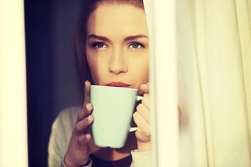 Beautiful woman drinking hot coffee or tea.