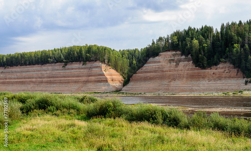 Geological outcrop on the riverbank with deep ravine - 77192369