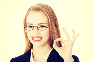 Beautiful business woman showing perfect sign.