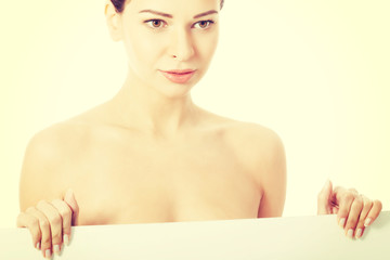 Topless woman holding copy space.