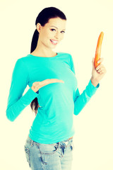 Beautiful woman holding fresh carrot.