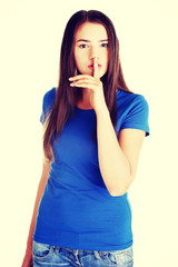 Young woman with finger on lips.