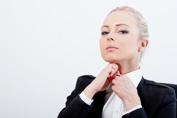 blonde executive buttons up her shirt