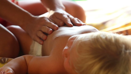 small blonde baby girl lies on bed and mother stroking her tummy