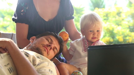 blonde baby girl hold ball and smile watching cartoons on laptop