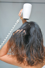 woman is blowing her hair with hair dryer