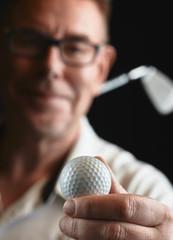 Mature man golfer and golf ball