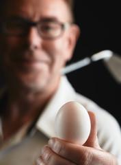 Mature man golfer and white egg