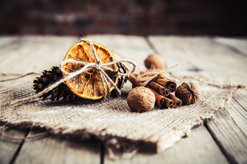 Dried orange tied with pine cones and nuts on a wooden backgroun