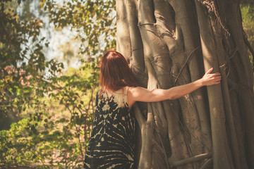 Woman hugging a giant tree
