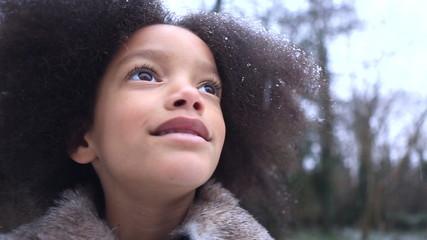 Little girl enjoying the snowflakes falling around her