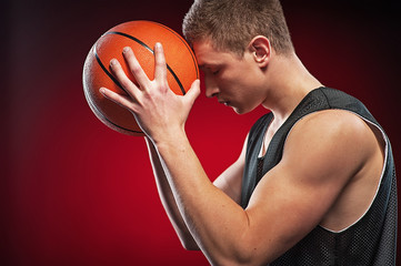 Caucasian male basketball player pressing ball to his forehead