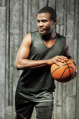 Afro-american male basketball player holding ball