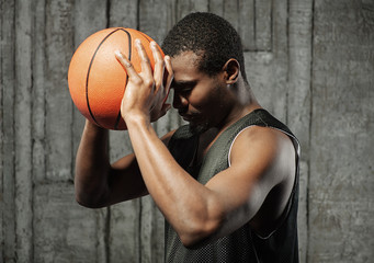 Afro-american basketball player pressing ball to his forehead